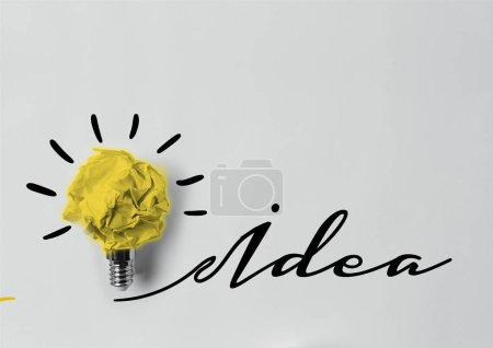 Photo for Top view of crumpled paper as light bulb with idea lettering - Royalty Free Image