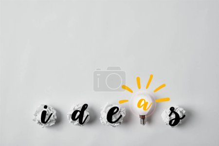 row of light bulb with crumpled papers and ideas word on white surface