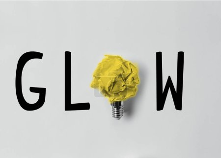 top view of crumpled paper as light bulb with glow word