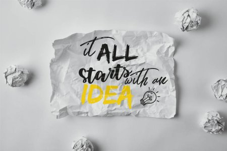 "top view of damaged paper with ""it all starts with an idea"" inspiration surrounded with crumpled papers on white surface"