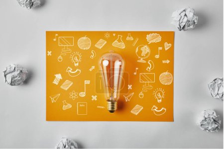 top view of incandescent lamp on blank yellow paper with business icons surrounded with crumpled papers on white surface