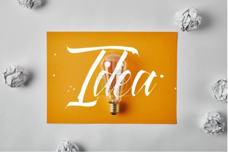 Idea concept with top view of incandescent lamp on blank yellow paper surrounded with crumpled papers