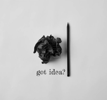 """Photo for Top view of black crumpled paper and pencil with """"got idea?"""" lettering on white surface - Royalty Free Image"""