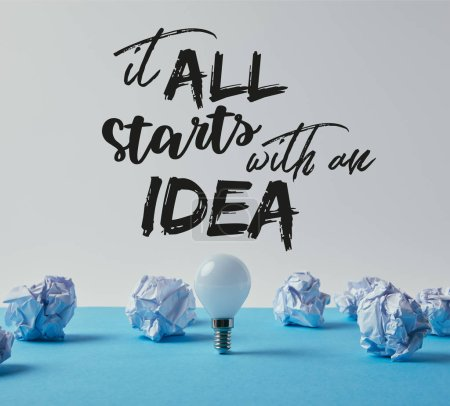 "light bulb with crumpled papers on blue surface with ""it all starts with an idea"" inspiration"