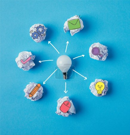 top view of light bulb surrounded with crumpled papers with business icons on blue surface