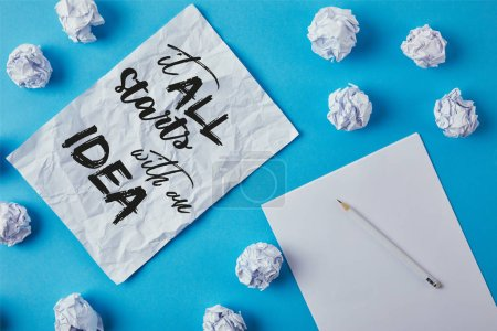 "top view of crumpled papers and pencil with ""it all starts with an idea"" inspiration on paper"