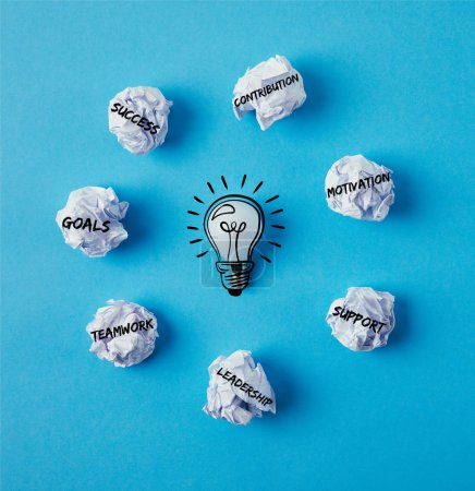 top view of light bulb surrounded with crumpled papers with business ideas on blue surface
