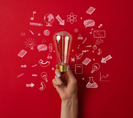 cropped shot of woman holding vintage incandescent lamp with business icons on red surface