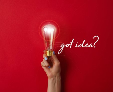 "woman holding vintage incandescent lamp on red surface with ""got idea?"" lettering"
