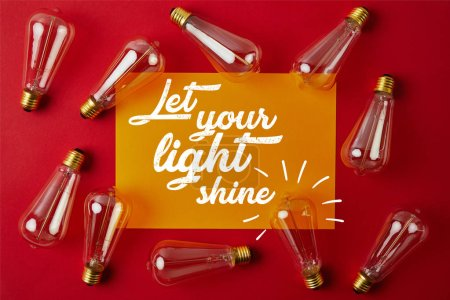 "Photo for Top view of vintage incandescent lamps on red surface with yellow paper and ""let your light shine"" inspiration - Royalty Free Image"