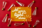 top view of vintage incandescent lamps on red surface with yellow paper and
