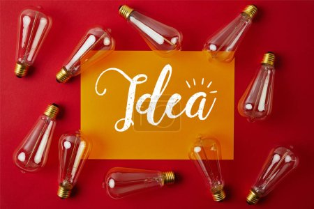 "Photo for Top view of vintage incandescent lamps on red surface with yellow paper and ""idea"" sign - Royalty Free Image"