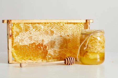 close up view of wooden honey deeper, glass jar with honey and stack of beeswax on white tabletop