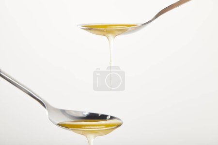 close up view of spoons with honey on white background