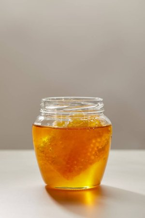 close up view of opened glass jar with honey and beeswax on grey background
