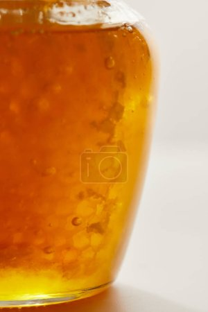 close up view of honey and beeswax in glass jar on white background