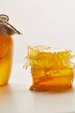 close up view of pile of beeswax and glass jar with honey on white tabletop