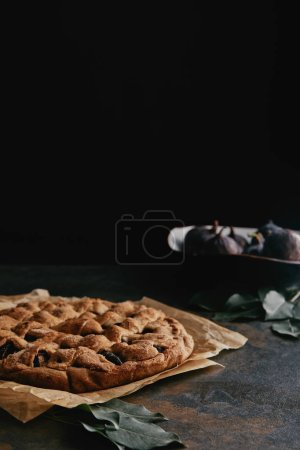 close up view of homemade pie on baking paper and fresh figs on dark tabletop