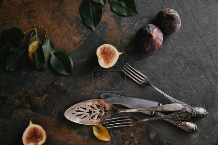 top view of antique cutlery, green leaves and figs on grungy surface