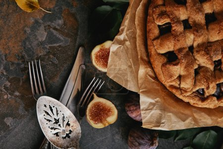 Photo for Top view of homemade pie on baking paper, antique cutlery and fresh figs on dark tabletop - Royalty Free Image