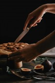cropped shot of woman cutting pie on baking paper with knife on surface with figs