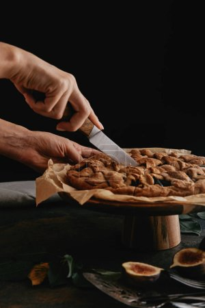 cropped shot of woman cutting pie on baking paper with knife on tabletop with figs