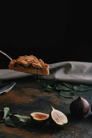 close up view of piece of pie on cake server and figs on dark grungy surface with black background