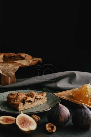 close up view of baked pie, beeswax and figs arranged on dark surface