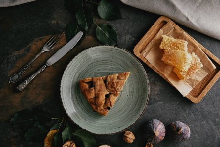 flat lay with piece of pie on plate, beeswax, figs and cutlery on grungy tabletop