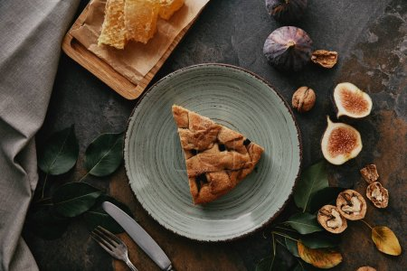 Photo for Flat lay with piece of pie on plate, beeswax, figs and cutlery on grungy tabletop - Royalty Free Image