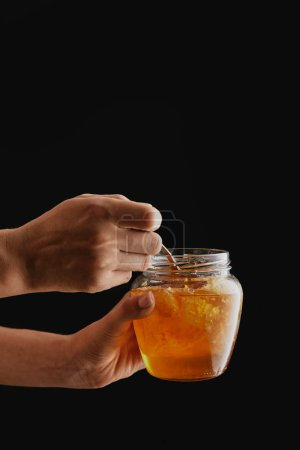 Photo for Partial view of woman holding glass with natural honey isolated on black - Royalty Free Image