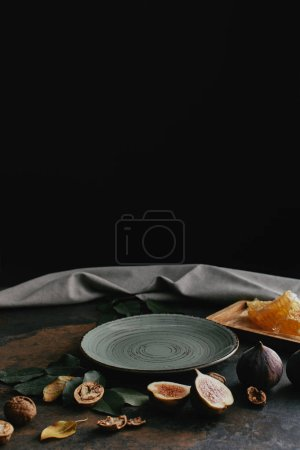 close up view of empty plate, hazelnuts, honey and figs arranged on grungy tabletop with black background