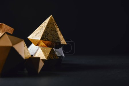 Photo for Cose-up view of shiny faceted glittering gold pieces on black background - Royalty Free Image