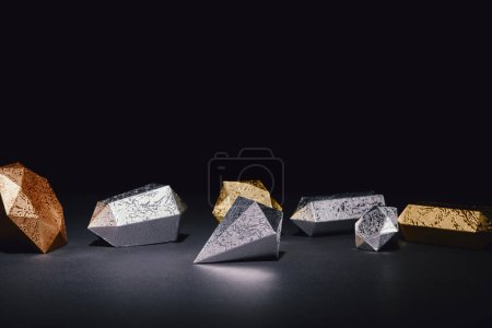 shiny pieces of silver and gold on black background