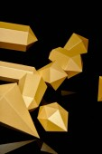 close-up view of shiny faceted pieces of gold reflected on black