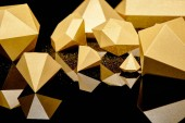 glittering faceted pieces of gold reflected on black background
