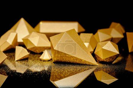 close-up view of glittering pieces of gold and golden dust reflected on black