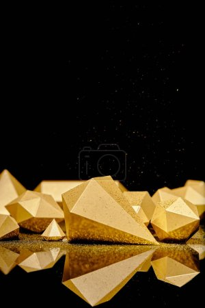 shiny glittering pieces of gold and golden dust reflected on black background