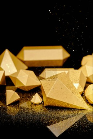 close-up view of shiny glittering pieces of gold and golden dust on black