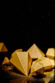 close-up view of shiny faceted golden pieces and dust on black