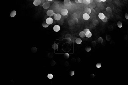 Photo pour Des étincelles bokeh décoratif argenté sur fond noir - image libre de droit