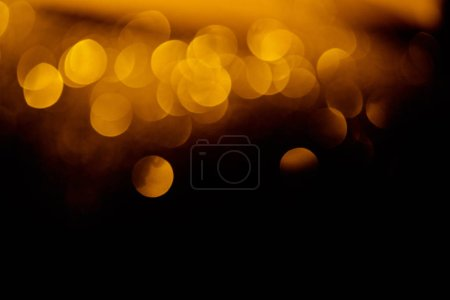 festive golden bokeh on black background with copy space