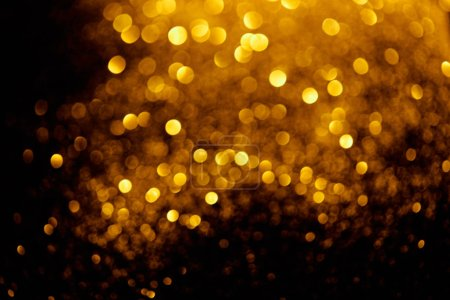 abstract background with blurred glowing golden glitter