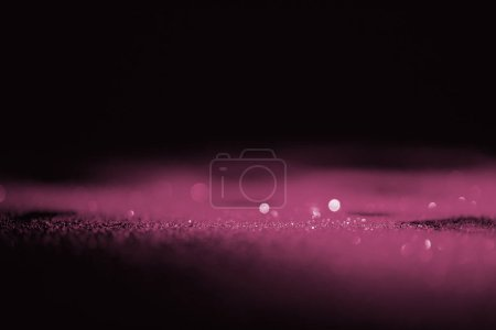 abstract shiny pink glitter on dark background with copy space