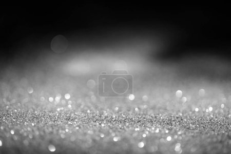 Photo pour Abstraite floue des paillettes argent brillant sur fond sombre - image libre de droit