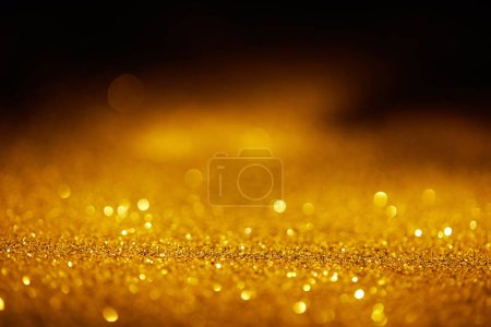 Photo for Abstract blurred golden glitter on dark background - Royalty Free Image