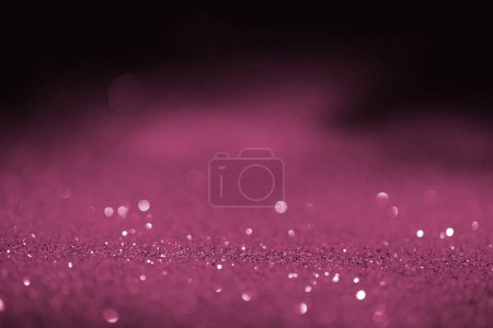 abstract blurred pink glitter on dark background