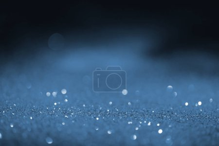 blurred blue glowing glitter on black background