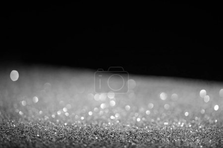 blurred silver glowing glitter on black background