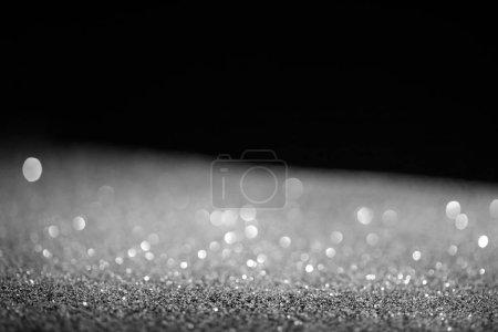 Photo pour Floue glitter brillant argenté sur fond noir - image libre de droit